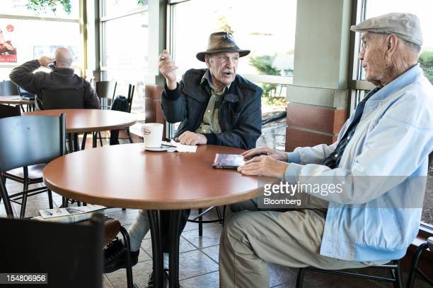 Steve Drazich center talks with his cousin Nick Drazich over coffee at a Tim Hortons Inc restaurant in Wintersville Ohio US on Thursday Oct 25 2012...