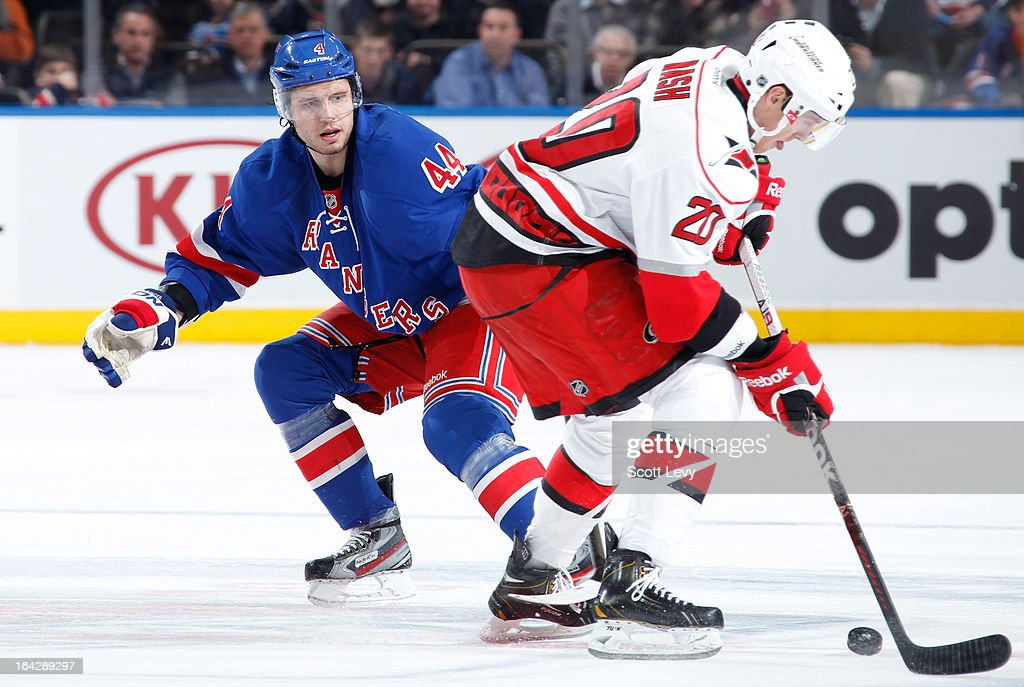 Steve Eminger of the New York Rangers attempts to poke the puck away from Riley Nash of the Carolina Hurricanes at Madison Square Garden on March 18...