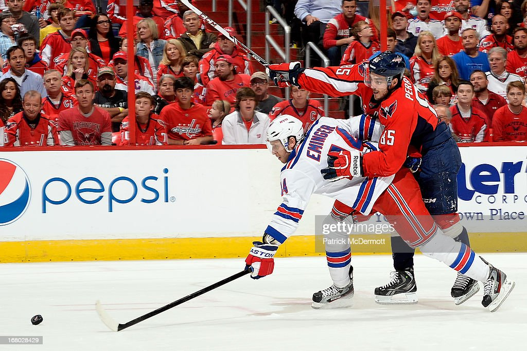 Steve Eminger of the New York Rangers battles for the puck against Mathieu Perreault of the Washington Capitals in the second period of Game Two of...