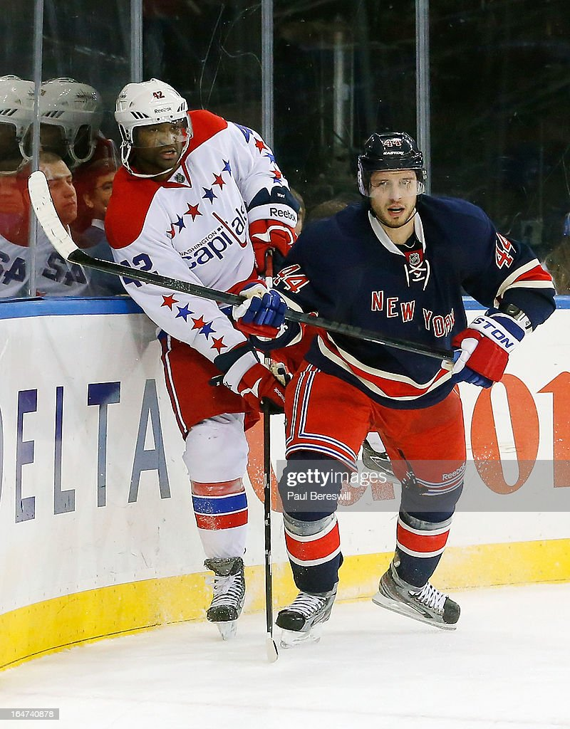 Steve Eminger of the New York Rangers checks Joel Ward of the Washington Capitals in an NHL hockey game at Madison Square Garden on March 24 2013 in...