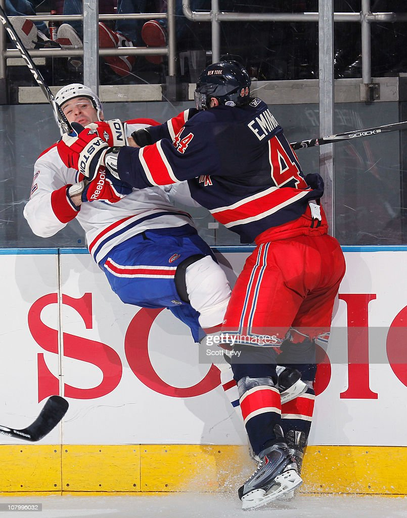 Steve Eminger of the New York Rangers checks Mathieu Darche of the Montreal Canadiens into the boards in the third period on January 11 2011 at...