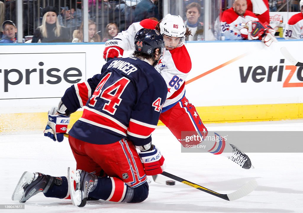 Steve Eminger of the New York Rangers defends against Mathieu Perreault of the Washington Capitals at Madison Square Garden on February 12 2012 in...