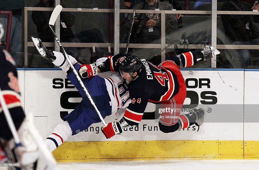 Steve Eminger of the New York Rangers finishes a check against Lars Eller of the Montreal Canadiens on January 11 2011 at Madison Square Garden in...