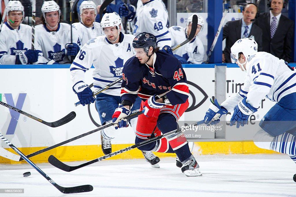 Steve Eminger of the New York Rangers skates under pressure by Nikolai Kulemin of the Toronto Maple Leafs at Madison Square Garden on April 10 2013...