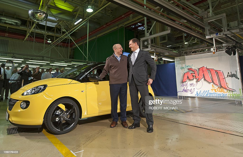 Steve Girsky, Chairman of the Opel Supervisory Board and Thomas Sedran, Vice CEO of German car maker Opel gesture as they present a newly fabricated Opel Adam car during the opening ceremony at the Opel plant in Eisenach, eastern Germany on January 10, 2013. The new Opel model will be produced as of January 10, 2013 at the Eisenach Opel plant and is intended to attract young automobile drivers in cities. Opel has already received 16 000 orders for the Adam. AFP PHOTO / ROBERT MICHAEL