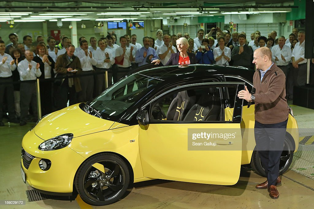Steve Girsky, General Motors Vice Chairman and head of GM Europe, and German athlete Ariane Friedrich emerge from an Opel Adam car after driving it from the assembly line as factory workers look on during a celebration to mark the launch of the new Opel compact car at the Opel factory on January 10, 2013 in Eisenach, Germany. Opel employees hope the car will help the compny return to profits after years of sagging sales and the announcement of the Bochum factory closure in 2016.