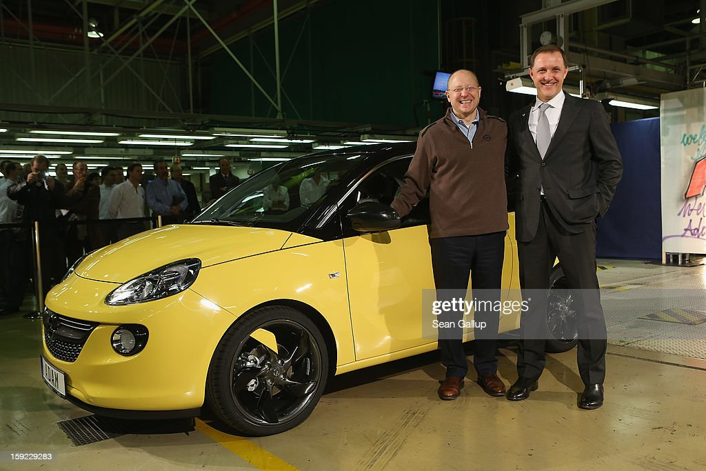 Steve Girsky (L), General Motors Vice Chairman and head of GM Europe, and Thomas Sedran, Deputy Chairman of Adam Opel AG, stand next to an Opel Adam car fresh from the assembly line as factory workers look on during a celebration to mark the launch of the new Opel compact car at the Opel factory on January 10, 2013 in Eisenach, Germany. Opel employees hope the car will help the compny return to profits after years of sagging sales and the announcement of the Bochum factory closure in 2016.