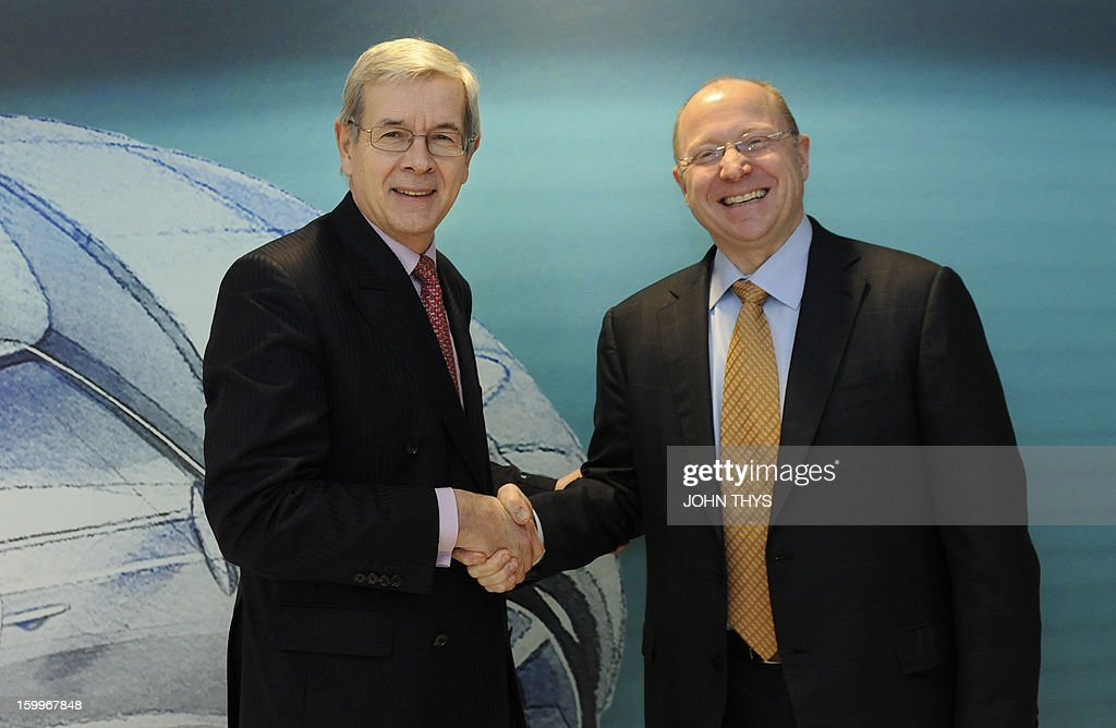 Steve Girsky (R), General Motors (GM) Vice Chairman, interim President of GM Europe and Chairman of the Opel Supervisory Board and the head of French carmaker PSA Peugeot, Philippe Varin (L) shake hands before a joint press briefing in Brussels on January 24, 2013.