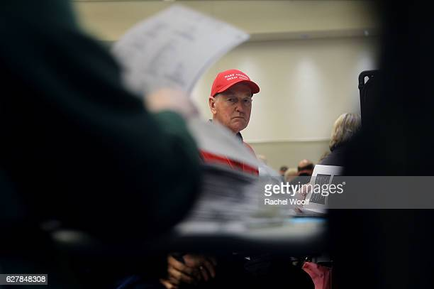 Steve Hargis wearing a 'Make America Great Again' hat watches as volunteers and city officials participate in a recount at the Oakland Schools...