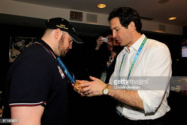 Steve Holcomb driver of the gold medal winning United States men's 4man bobsleigh team shows his medal to NHL great Brendan Shanahan during the men's...