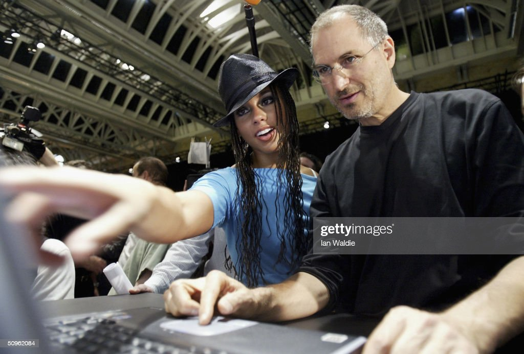 Steve Jobs, Chief Executive Officer of Apple computers (R) demonstrates iTunes to R&B singer Alicia Keys as he launches iTunes Music Store in the territories of Great Britain, Germany and France, on June 15, 2004 in London. The iTunes store allows users to buy and download albums or individual songs from a library of 700,000 songs.