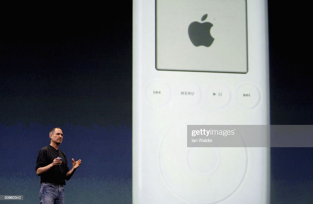 Steve Jobs, Chief Executive Officer of Apple computers, stands by a projection of an iPod as he launches iTunes Music Store in the territories of Great Britain, Germany and France, on June 15, 2004 in London. The iTunes store allows users to buy and download albums or individual songs from a library of 700,000 songs.
