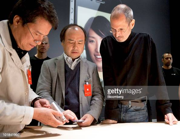 Steve Jobs chief executive officer of Apple Inc right speaks with Masayoshi Son chief executive officer of Softbank Corp and Mitz Kurobe at the Apple...
