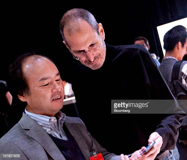 Steve Jobs chief executive officer of Apple Inc right speaks with Masayoshi Son chief executive officer of Softbank Corp about the iPhone 4 during...