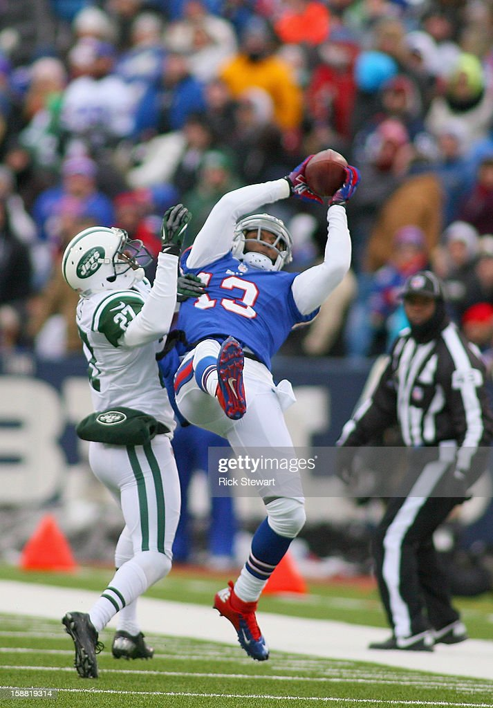 Steve Johnson #13 of the Buffalo Bills makes a 37 yard catch against Darrin Walls #27 of the New York Jets at Ralph Wilson Stadium on December 30, 2012 in Orchard Park, New York. The catch put Johnson over 1000 yards receiving for the year. Buffalo won 28-9.