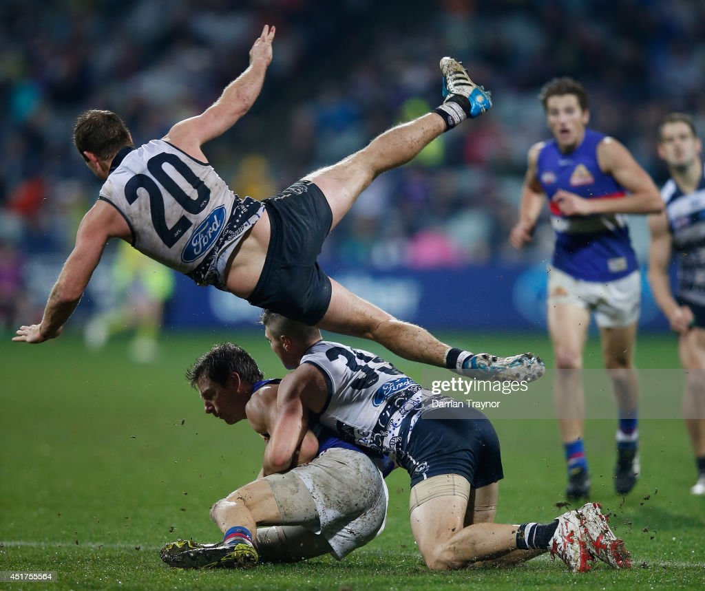 Steve Johnson of the Cats jumps over Dale Morris of the Bulldogs and Shane Kersten of the Cats during the round 16 AFL match between the Geelong Cats and the Western Bulldogs at Skilled Stadium on July 6, 2014 in Melbourne, Australia.