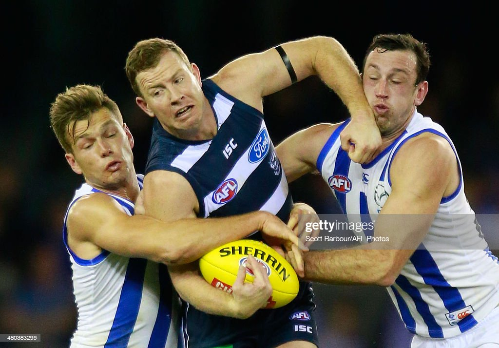 Steve Johnson of the Geelong Cats is tackled by Shaun Higgins of the North Melbourne Kangaroos and Todd Goldstein of the North Melbourne Kangaroos during the round 15 AFL match between the North Melbourne Kangaroos and the Geelong Cats at Etihad Stadium on July 11, 2015 in Melbourne, Australia.
