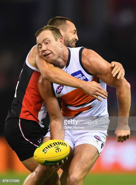 Steve Johnson of the Giants handballs whilst being tackled Jarryn Geary of the Saints during the round seven AFL match between the St Kilda Saints...