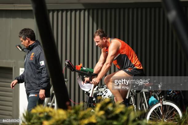 Steve Johnson of the Giants rides a bike as Giants head coach Leon Cameron looks on during a Greater Western Sydney Giants AFL training session at...