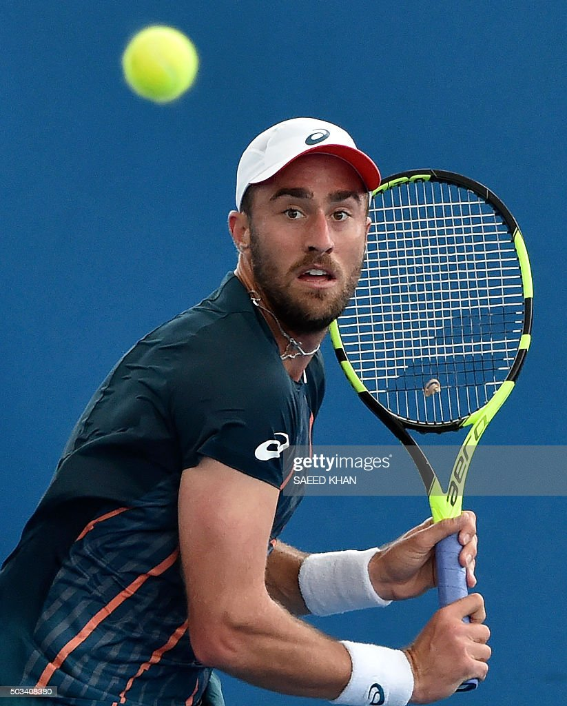 Steve Johnson of the US hits a return against Viktor Troicki of