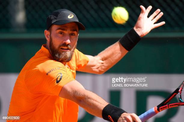 US Steve Johnson returns the ball to Croatia's Borna Coric during their tennis match at the Roland Garros 2017 French Open on May 31 2017 in Paris /...