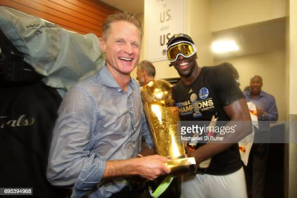 Steve Kerr and Draymond Green of the Golden State Warriors celebrate with the Larry O'Brien Trophy in the locker room after winning the NBA...