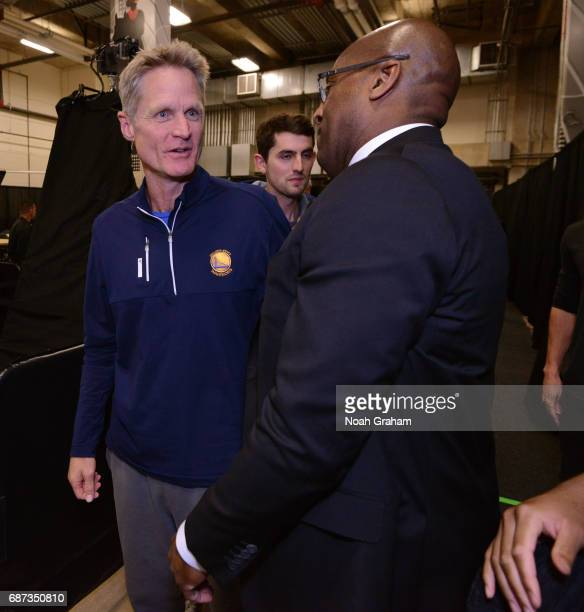 Steve Kerr and Mike Brown of the Golden State Warriors talk in the hallway after winning Game Four of the Western Conference Finals against the San...