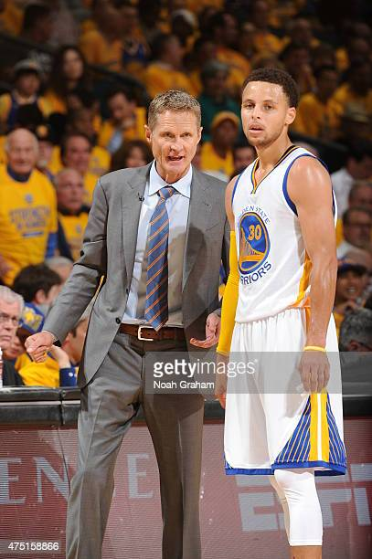 Steve Kerr and Stephen Curry of the Golden State Warriors speak during a game against the Houston Rockets in Game Five of the Western Conference...