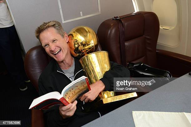 Steve Kerr of the Golden State Warriors holds the NBA trophy on the plane as the team travels home from Cleveland after winning the 2015 NBA Finals...