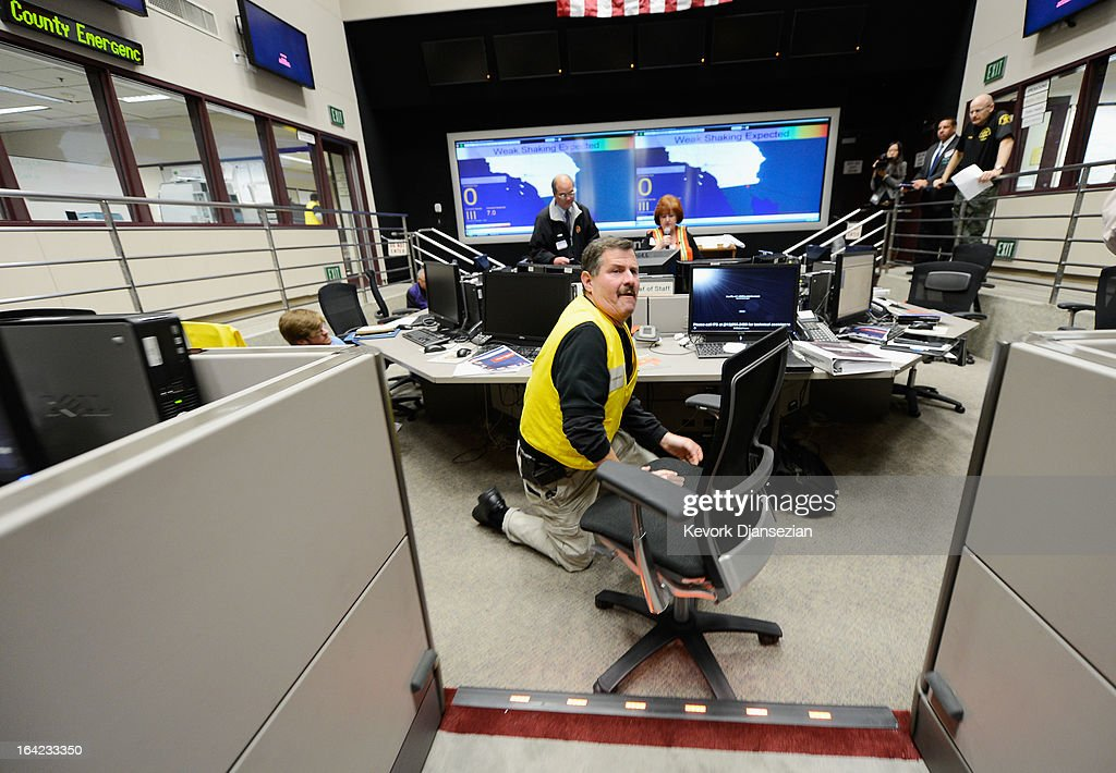 Steve Lieberman, assistant administrator of The County of Los Angeles Office of Emergency Management, takes cover under his desk during a simulated magnitude 7.0 aftershock following a simulated 7.8 magnitude earthquake during a functional exercise at the Los Angeles County Emergency Operations Center (CEOC) hosted by The County of Los Angeles Office of Emergency Management on March 21, 2013 in Los Angeles, California. The training exercise featured the California Integrated Seismic Network's Earthquake Ready Warning Demonstration System, which included 88 cities, 137 unincorporated communities, 200 schools and several nonprofit organizations.