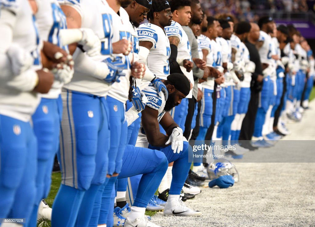 Steve Longa #54 of the Detroit Lions takes a knee with teammate Jalen Reeves-Maybin during the national anthem before the game against the Minnesota Vikings on October 1, 2017 at U.S. Bank Stadium in Minneapolis, Minnesota.