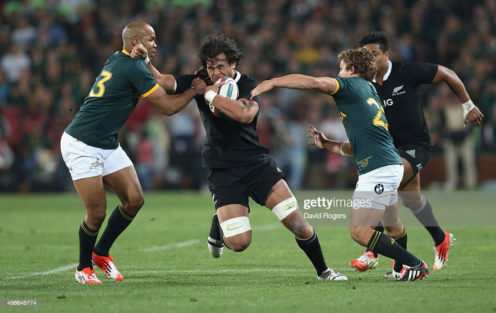 Steve Luatua of the All Blacks is tackled by JP Pietersen and Patrick Lambie during the Rugby Championship match between the South African Springboks...
