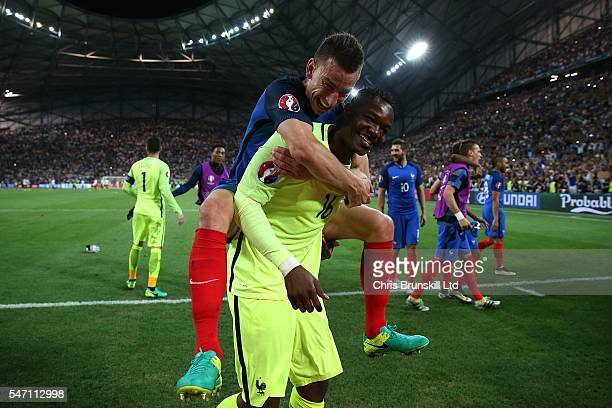 Steve Mandanda of France celebrates with teammate Laurent Koscielny at fulltime following the UEFA Euro 2016 Semi Final match between Germany and...
