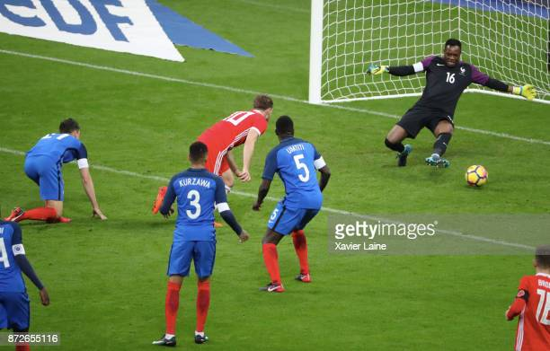 Steve Mandanda of France stop the ball over Aaron Ramsey of Wales during the friendly match between France and Wales at Stade de France on November...