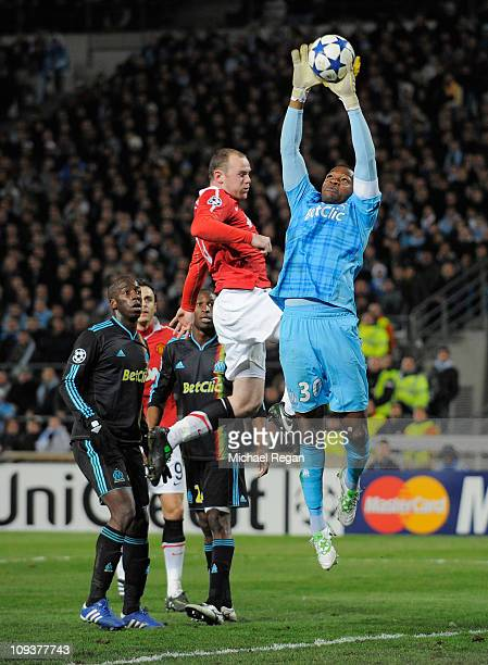Steve Mandanda of Marseille claims the ball under a challenge by Wayne Rooney of Manchester United during the UEFA Champions League round of 16 first...