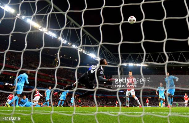Steve Mandanda of Marseille fails to stop Jack Wilshere of Arsenal score the opening goal during the UEFA Champions League Group F match between...