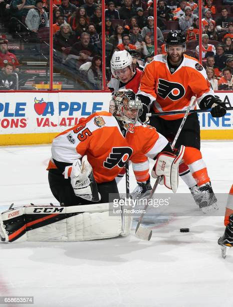 Steve Mason and Andrew MacDonald of the Philadelphia Flyers clear the puck from the crease against Brock McGinn of the Carolina Hurricanes on March...