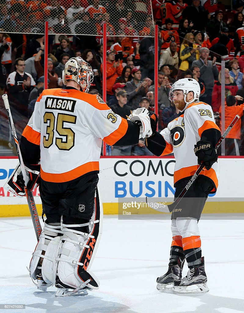 Steve Mason #35 and Claude Giroux #28 of the Philadelphia Flyers celebrate the win over the Chicago Blackhawks on December 3, 2016 at Wells Fargo Center in Philadelphia, Pennsylvania.The Philadelphia Flyers defeated the Chicago Blackhawks 3-1.Today was Claude Giroux's 600th NHL game.