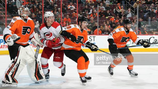 Steve Mason Ivan Provorov and Andrew MacDonald of the Philadelphia Flyers defend Brock McGinn of the Carolina Hurricanes on March 19 2017 at the...