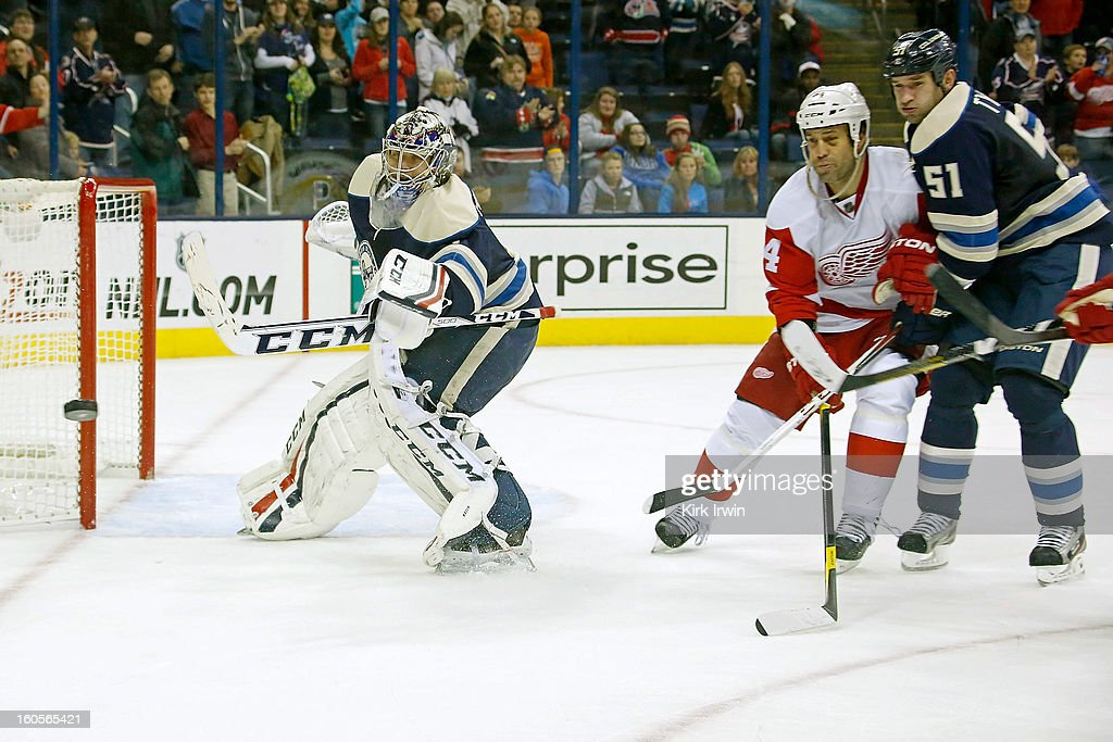 Steve Mason #1 of the Columbus Blue Jackets makes a save and flips the rebound away from <a gi-track='captionPersonalityLinkClicked' href=/galleries/search?phrase=Todd+Bertuzzi&family=editorial&specificpeople=202476 ng-click='$event.stopPropagation()'>Todd Bertuzzi</a> #44 of the Detroit Red Wings as <a gi-track='captionPersonalityLinkClicked' href=/galleries/search?phrase=Fedor+Tyutin&family=editorial&specificpeople=215245 ng-click='$event.stopPropagation()'>Fedor Tyutin</a> #51 of the Columbus Blue Jackets comes to back to help on defense during the third period on February 2, 2013 at Nationwide Arena in Columbus, Ohio. Columbus defeated Detroit 4-2.