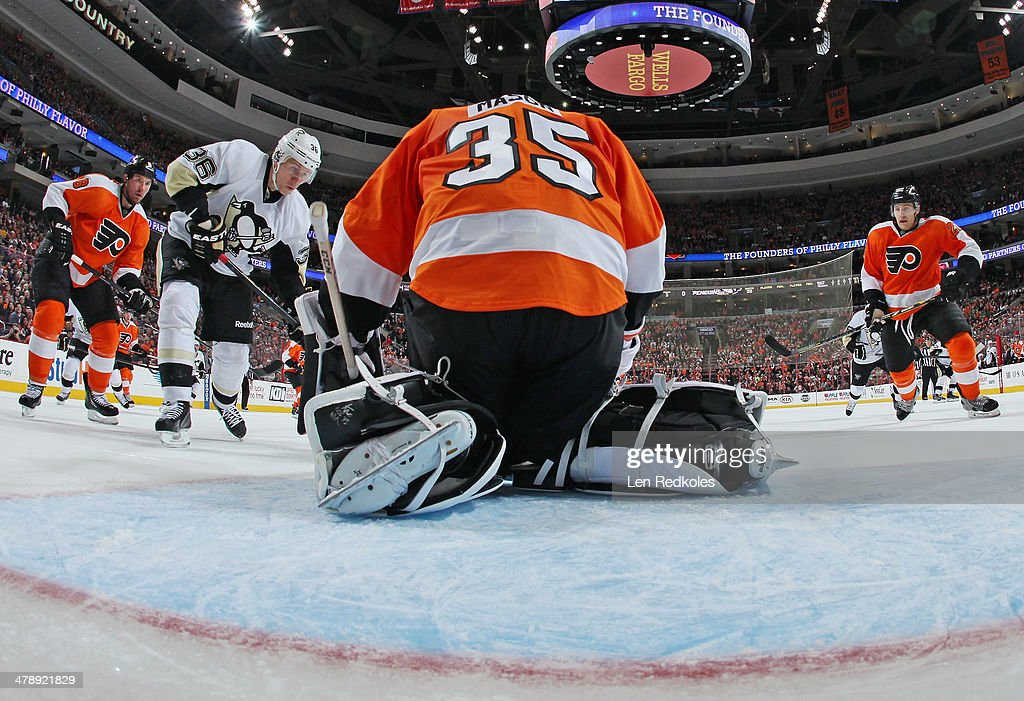 Steve Mason #35 of the Philadelphia Flyers covers the puck as teammates Nicklas Grossmann #8 and Luke Schenn #22 skate in to defend against Jussi Jokinen #36 of the Pittsburgh Penguins on March 15, 2014 at the Wells Fargo Center in Philadelphia, Pennsylvania. The Flyers went on to defeat the Penguins 4-0.