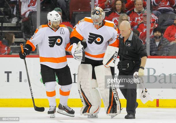 Steve Mason of the Philadelphia Flyers is helped off the ice in the third period after an injury against the New Jersey Devils by teammate...