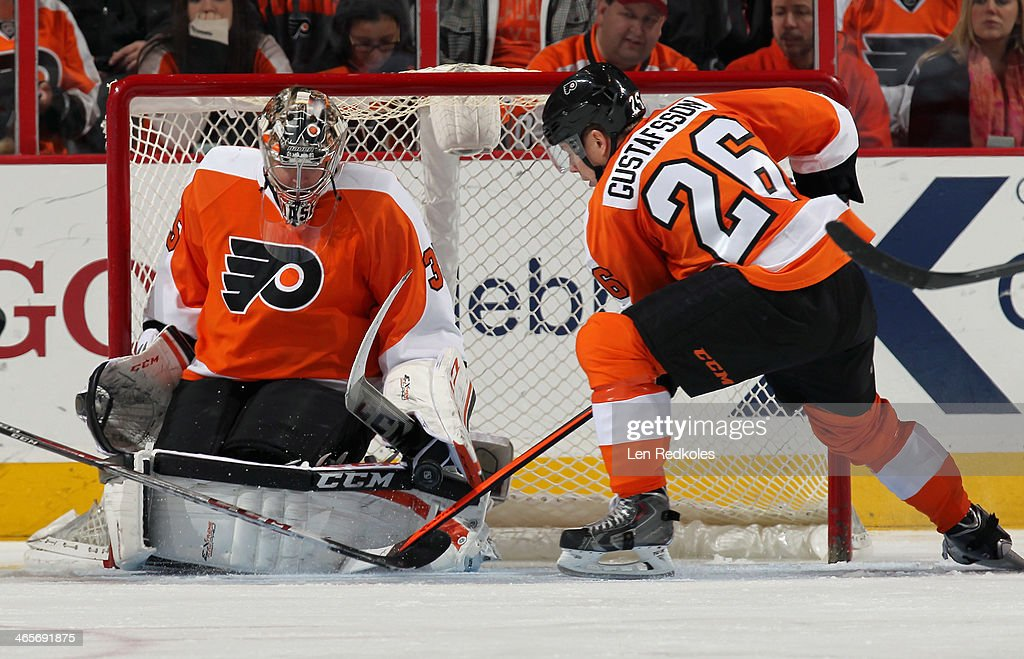 Steve Mason #35 of the Philadelphia Flyers makes a pad save as <a gi-track='captionPersonalityLinkClicked' href=/galleries/search?phrase=Erik+Gustafsson+-+Ice+Hockey+Player+-+Born+1988&family=editorial&specificpeople=10836949 ng-click='$event.stopPropagation()'>Erik Gustafsson</a> #26 attempts to control the rebound against the Detroit Red Wings on January 28, 2014 at the Wells Fargo Center in Philadelphia, Pennsylvania. The Flyers went on to defeat the Red Wings 5-0.