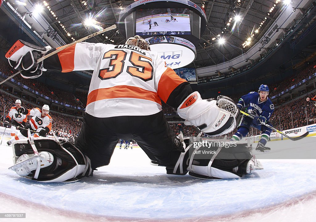 Steve Mason #35 of the Philadelphia Flyers makes a save on David Booth #7 of the Vancouver Canucks during an NHL game at Rogers Arena December 30, 2013 in Vancouver, British Columbia, Canada. Philadelphia won 4-3.