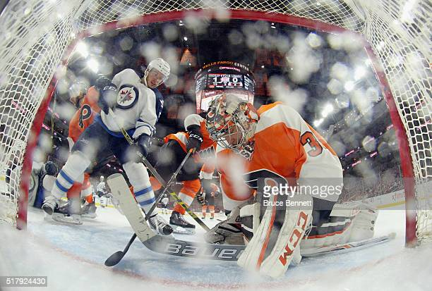 Steve Mason of the Philadelphia Flyers makes the save as Marko Dano of the Winnipeg Jets looks for the rebound at the Wells Fargo Center on March 28...