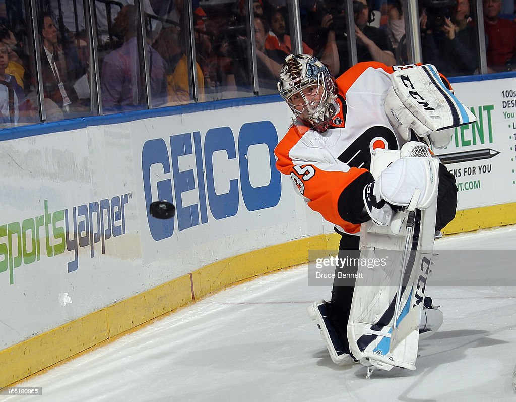 Steve Mason #35 of the Philadelphia Flyers shoots the puck around the boards during the game against the New York Islanders at the Nassau Veterans Memorial Coliseum on April 9, 2013 in Uniondale, New York. The Islanders defeated the Flyers 4-1.