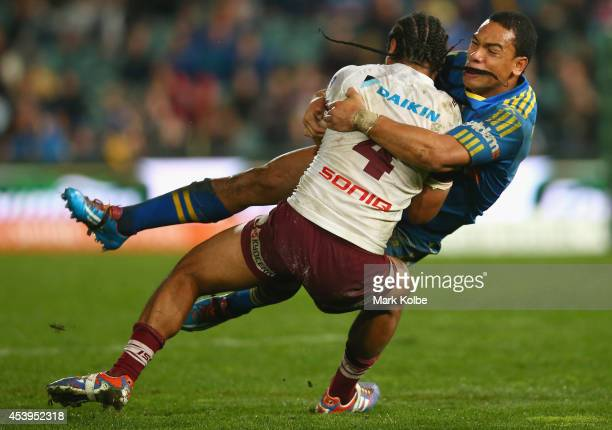 Steve Matai of the Sea Eagles is tackled by Will Hopoate of the Eels during the round 24 NRL match between the Parramatta Eels and the Manly Sea...