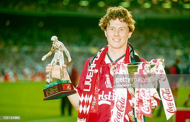 Steve McManaman of Liverpool is man of the match and holds his award in his right hand and the CocaCola Cup League Cup trophy in his left following...
