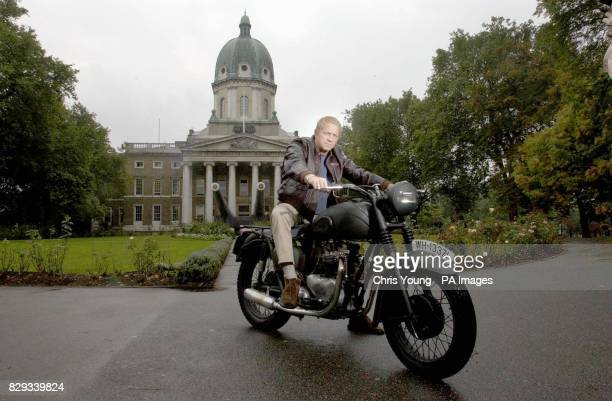 Steve McQueen lookalike Mark Myers poses with a replica of the Triumph motorcycle used in the film 'The Great Escape' outside the Imperial War Museum...