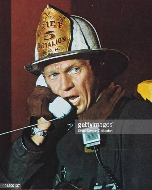 Steve McQueen US actor speaking into a white telephone receiver and wearing a firefighter's costume in a publicity still issued for the film 'The...